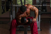 Shirtless bodybuilder doing heavy weight exercise for biceps — Stock Photo