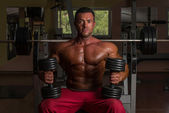 Shirtless body builder posing with dumbbell at the bench — Stock Photo