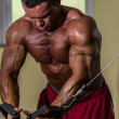 Shirtless body builder doing standing press white cable for chest — Stockfoto