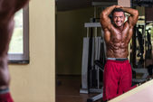 Bodybuilder showing abs at mirror — Stock Photo