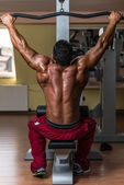 Shirtless bodybuilder doing heavy weight exercise for back — Stock Photo