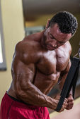 Bodybuilder doing heavy weight exercise for triceps with cable — Stock Photo