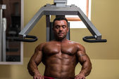 Bodybuilder resting after doing heavy weight exercise — Stock Photo