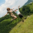 Mother and son jumping in meadow — Stock Photo #27233989