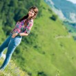 Beautiful woman in jeans standing on the grass — Stock Photo