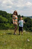 мать и сын, стоя на траве — Стоковое фото