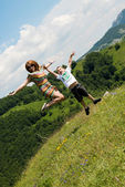 Mother and son jumping in meadow — Stock Photo