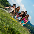 Group of girls sitting on grass and having fun — Stock Photo