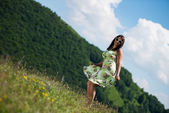Young woman in dress standing on the grass — Stock Photo