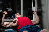 Young bodybuilder doing bench press for chest — Stock Photo