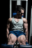 Bodybuilder doing heavy weight exercise for legs on machine leg extensions — Stock Photo
