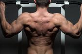 Junge männliche bodybuilder handeln schweres übung — Stockfoto