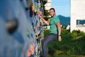 Young man climbing wall rock outdoors — Stock Photo