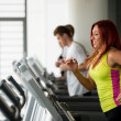 Young woman running on treadmills — Stock Photo