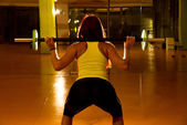Young Woman doing squats with barbell — Foto de Stock