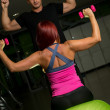Woman and Personal Trainer in gym with dumbbells — Stock Photo