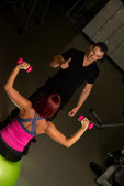 Young couple exercising at the fitness gym — Stock Photo