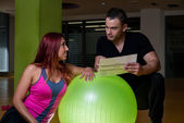 Adult female with personal trainer at gym — Stock Photo