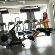 Young women on a rowing machine — Stock Photo