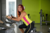 Happy woman working out on a gym cycle — Stock Photo