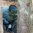 Paintball Players Hide Behind Tree — Stockfoto