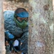 Paintball Players Hide Behind Tree — Photo
