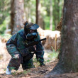 Stock Photo: Paintball Players Hide Behind Tree
