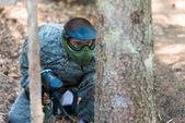 Paintball hráčů skrýt za stromem — Stock fotografie