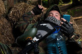 Paintball player resting and looking at the phone — Stock Photo