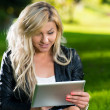 Young Woman using a digital tablet in the park — Stock Photo
