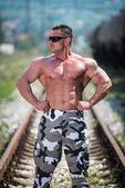 Body Builder Posing At The Railroad — Zdjęcie stockowe