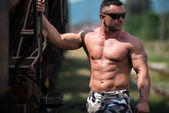Male Bodybuilder Holding On To Train — Stock Photo