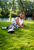 Man Lying On Grass And Holding Bottle Of Water — Stock Photo