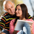 Male And Female Look At Electronic Tablet In Park — Stock Photo #35131383
