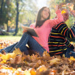 Young Couple With Headphones And Throwing Fall Leaves — Stock Photo #35136049