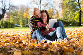 Beautiful Couple Sitting In Park And Using Tablet Computer — Stock Photo