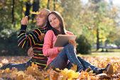 Couple Listening To Music On Autumn Leaves — Stock Photo