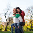 Man Carrying Woman Piggyback At Autumn Woods — Stock Photo