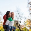 Male Carrying Smiling Female On His Back At Park — Stock Photo