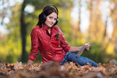 Young Girl With Headphones Enjoying Music In Autumn — ストック写真