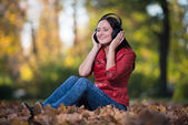 Girl Listening To Music On Autumn Leaves — Stok fotoğraf
