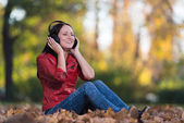 Girl Listening To Music On Autumn Leaves — Stock Photo