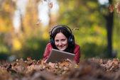 Jovem mulher deitada fora e ouvir com fones de ouvido — Fotografia Stock