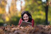 Young Woman Lying Outside And Listening To Headphones — ストック写真