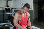 Jovem homem caucasiano muscular descansando no banco — Fotografia Stock