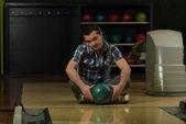 Wesoły młody człowiek posiadający kula do kręgli — Zdjęcie stockowe
