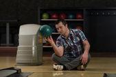 Alegre joven sosteniendo la bola de boliche — Foto de Stock