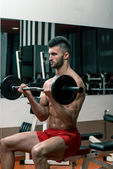 Men In The Gym Performing Biceps Curls With A Barbell — Stock Photo