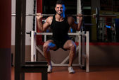 A Physically Fit Men Exercising By Doing Squats — Stock Photo