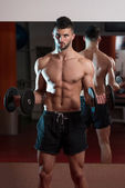 Young Man Lifting Dumbbell In Gym — Stock Photo